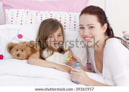 Sick little girl in bed taking cough medicine with her mother - stock photo