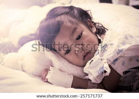 Sick little girl lay down on bed in the hospital - stock photo