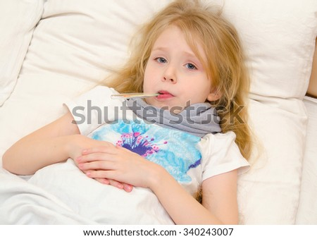 Sick little girl lying in the bed with thermometer in her mouth - stock photo