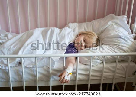 Sick little girl with an intravenous cannula in her hand, sleeping in hospital bed  - stock photo