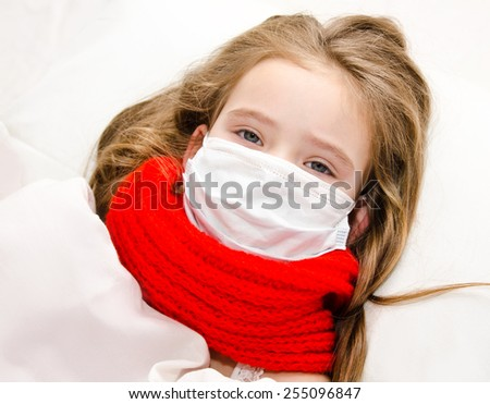 Sick little girl with surgical face mask for bacterial and virus flu protection and scarf in the bed - stock photo