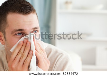 Sick man blowing his nose in his living room - stock photo
