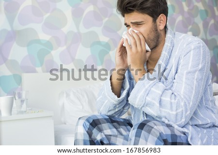 Sick man blowing his nose in tissue paper on bed at home - stock photo