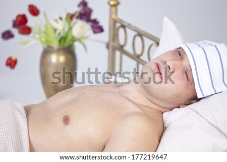Sick man lying on bed with pain in face - stock photo