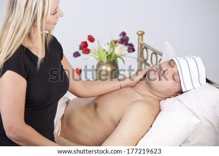 Sick man on bed - woman nursing him - stock photo