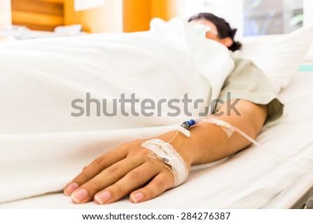 Sick man sleeping on bed at hospital - stock photo