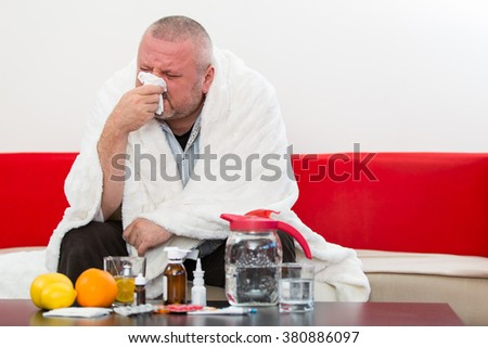Sick  man wearing pajama suffering cold and winter flu virus having medicine - stock photo