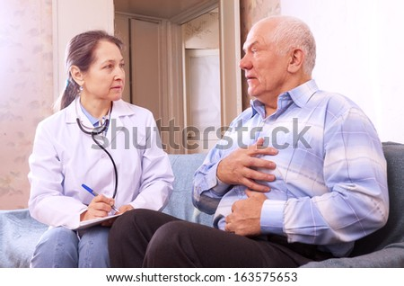 sick mature man complaining  to doctor about symptoms of malaise - stock photo