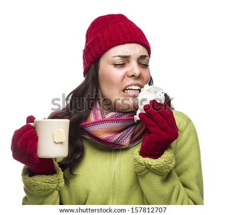 Sick Mixed Race Woman Wearing Winter Hat and Gloves Blowing Her Sore Nose and Holding Cup of Hot Tea Isolated on White.  - stock photo
