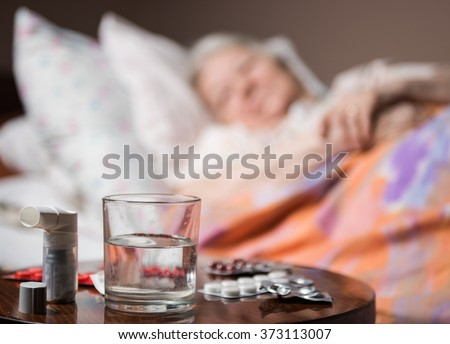 Sick old woman lying at bed bed with focus on medicine and glass of water in foreground - stock photo