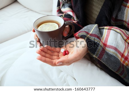 Sick person is taking medicines and drinking hot tea with lemon - stock photo
