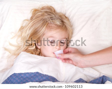 Sick preschooler taking medicine from a cup laying in bed - stock photo