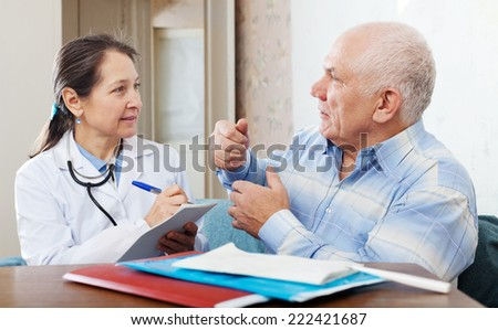 Sick senior man  complaining to doctor about malaise in interior - stock photo