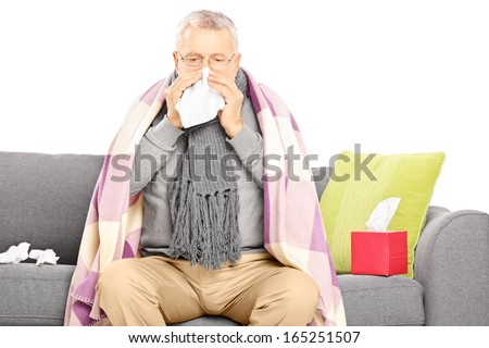 Sick senior man covered with blanket sitting on a sofa and blowing his nose isolated on white background - stock photo