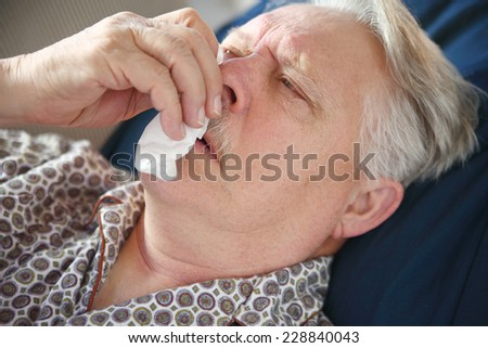 Sick senior man lies on sofa, and tends to his runny nose. - stock photo
