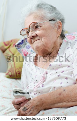 Sick senior woman in her bed - stock photo