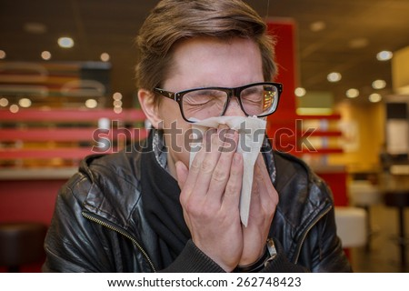 sick student blowing his nose into a tissue. - stock photo