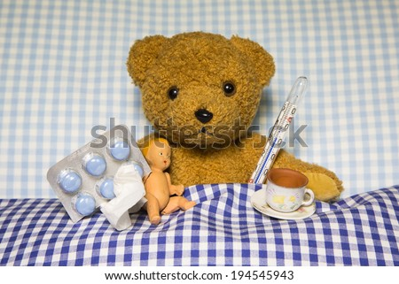 Sick teddy bear lying with medicaments in the bed. Concept for ill children. - stock photo