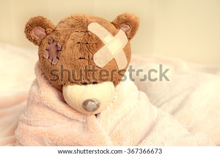 Sick teddy bear with patch in bed - stock photo