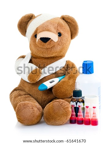Sick teddy bear wrapped in bandages with underarm thermometer and bottles of medicinal drugs, isolated on white background. - stock photo