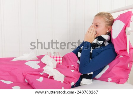 Sick teen girl laying in bed with tissues to blowing the nose - stock photo