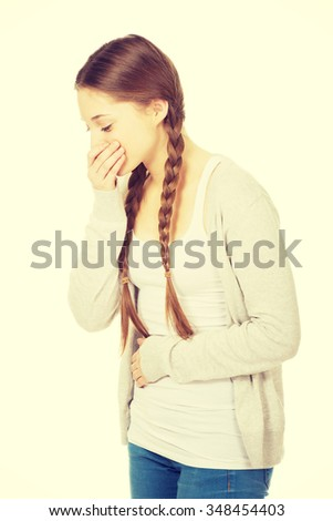 Sick teen woman about to vomit covering mouth. - stock photo