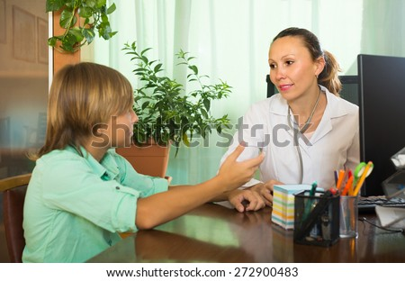 Sick teenager complaining to doctor about symptoms of malaise. Focus on woman - stock photo