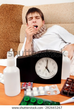 Sick Teenager take a Pill on the Bed at the Home - stock photo