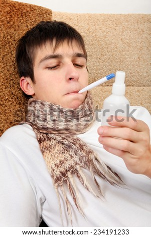 Sick Teenager with Thermometer and Drug on the Sofa at the Home - stock photo