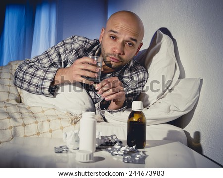 sick wasted man lying in bed at home wearing pajama suffering cold and winter flu virus taking medicine tablets in health care concept in tired face expression - stock photo