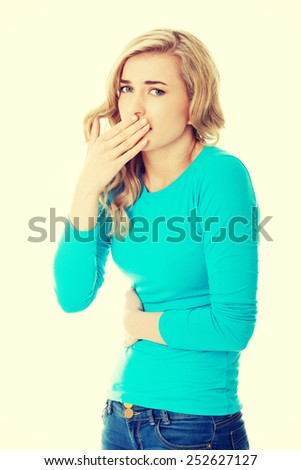 Sick woman about to throw up holding her stomach - stock photo