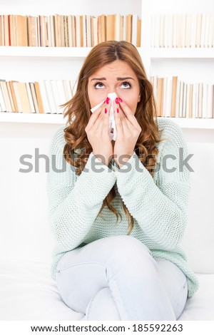 sick woman caught cold blowing her nose into handkerchief having flu or allergy - stock photo