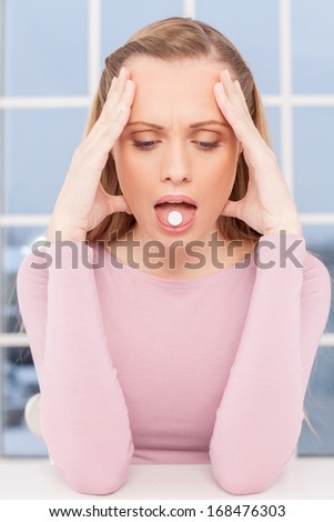 Sick woman. Depressed young woman touching head with hands and holding a pill on her tongue  - stock photo