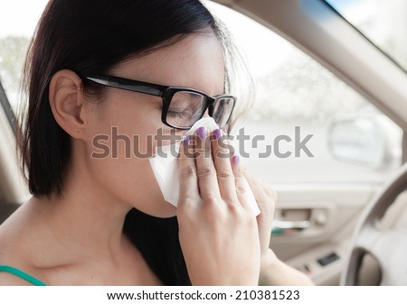 Sick woman driver. Woman driver sneezing in the car. - stock photo