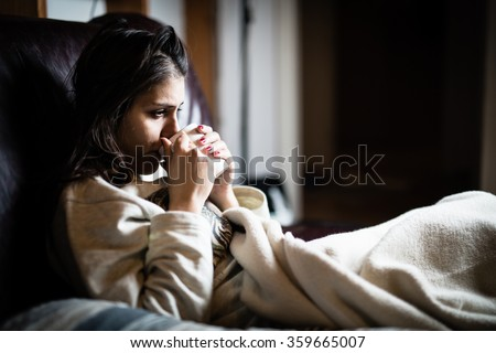 Sick woman in bed,calling in sick,day off from work.Drinking herbal tea.Vitamins and hot tea for flu.Woman Caught Cold.Virus. Dysentery.Diarrhea.Woman looking sick and tired - stock photo