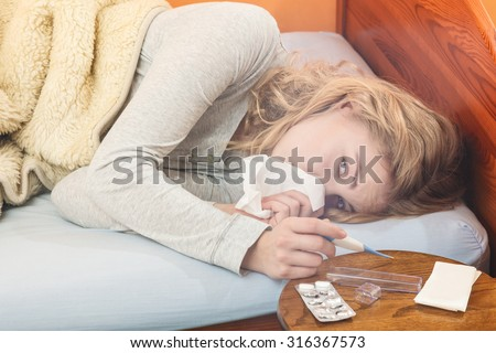 Sick woman laying in bed under wool blanket sneezing in tissue holding thermometer. Ill girl caught cold flu. Pills and tablets on table. - stock photo