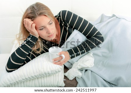 Sick woman laying on a sofa - stock photo