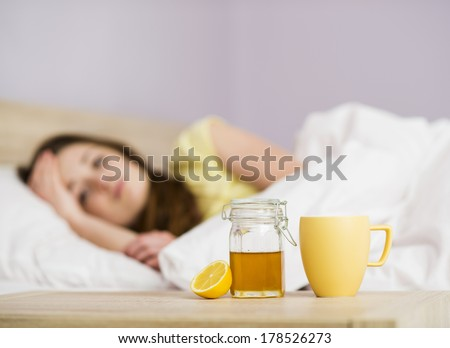 Sick woman lying in bed with high fever. She has cold and flu. In front of her is tea with lemon and honey. - stock photo