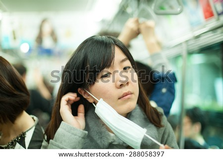 Sick woman wearing mask on her face.Travel on the train. - stock photo