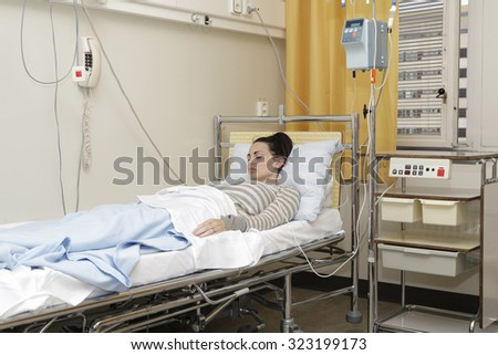 Sick woman with an IV drip in a hospital bed - stock photo