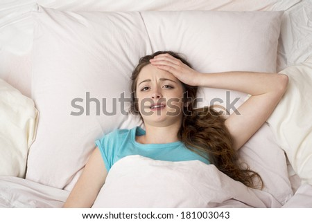 Sick woman with headache is lying in bed - stock photo