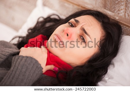 Sick woman with terrible sore throat. Closeup image of young woman with red nose lying in bed with thick scarf and touching her neck feeling pain - stock photo