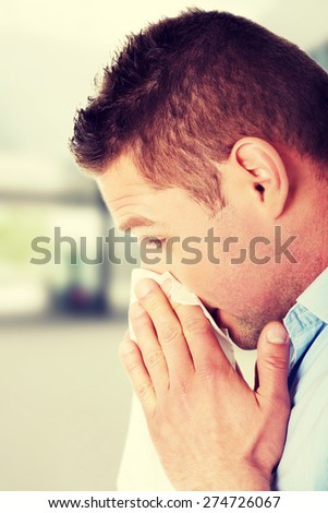 Sick young man blowing his nose - stock photo