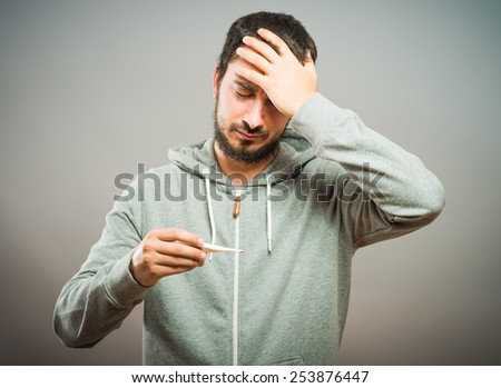 Sick young man looks at a thermometer - stock photo
