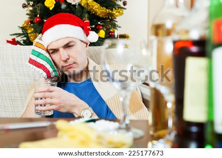 Sick young man with hangover sitting by table in Santa hat with glass of water in hand - stock photo