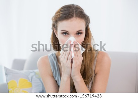 Sick young woman sitting on sofa blowing her nose at home in the sitting room - stock photo