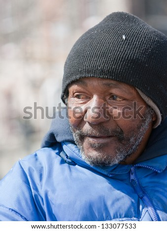 Side angle of homeless african american man outdoors during the daytime. - stock photo