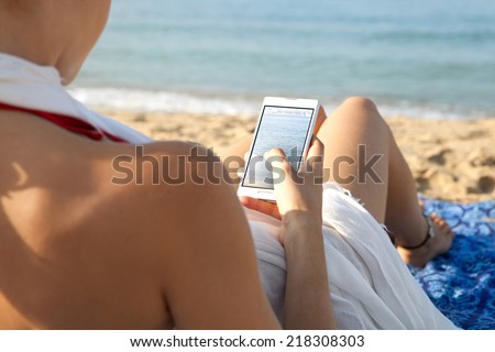 Side close up view of a young attractive woman on holiday laying down on a beach by the sea, holding and using a smartphone to take pictures of the scenery. People travel technology outdoors. - stock photo
