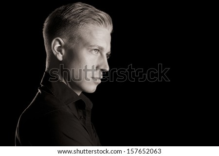 Side-face low key portrait of young handsome man in dark shirt looking up, black and white, isolated on black background. - stock photo