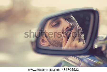 Side mirror view reflection sleepy tired fatigued yawning exhausted young man driving his car in traffic after long hour drive. Transportation sleep deprivation accident concept - stock photo